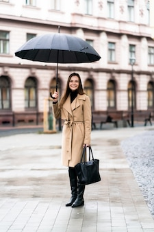 Foto all'aperto di signora bruna in posa con l'ombrello nero in una piovosa giornata autunnale. ritratto di moda street style. indossa pantaloni scuri casual, maglione bianco e cappotto cremoso. concetto di moda.