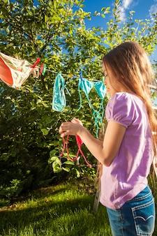 Foto all'aperto di una giovane ragazza che asciuga i panni sulla corda