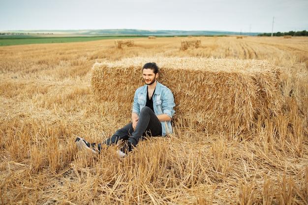 Foto all'aperto di un giovane ragazzo in giacca di jeans, seduto nel campo di grano.