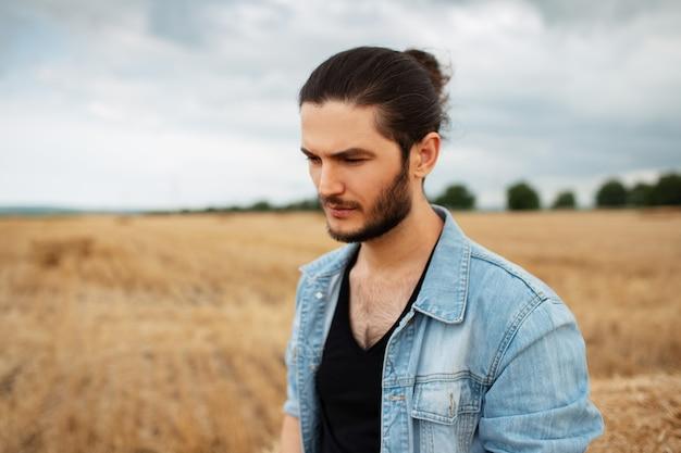 Foto all'aperto di giovane uomo in giacca blu, in piedi nel campo di grano.