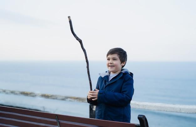 Ritratto all'aperto bambino attivo che gioca con il bastone di legno con il mare blu sfocato dell'oceano