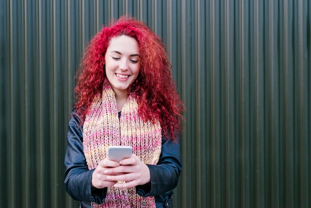 Ritratto all'aperto di giovane donna attraente con il telefono cellulare in strada.
