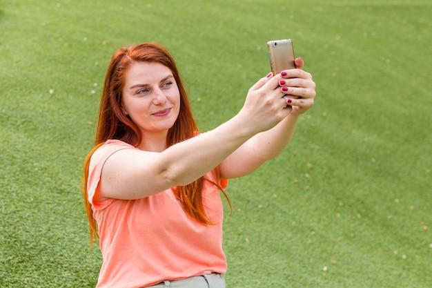 Ritratto all'aperto di bella ragazza dello zenzero che prende un selfie. felice giovane donna che utilizza smart phone all'aperto, ragazza seduta su una panchina nel parco e conduce trasmissioni in diretta.