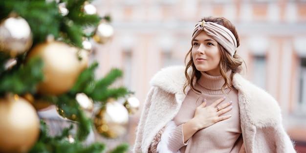 Ritratto esterno di bella ragazza contro un abete decorato. natale, capodanno, inverno
