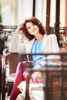 Outdoor ritratto di bella donna al tavolo in un caffè della città di strada.