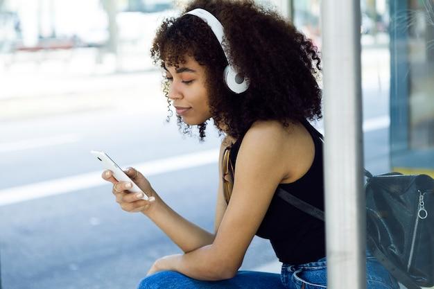 Ritratto all'aperto di bella giovane donna che ascolta la musica in città.