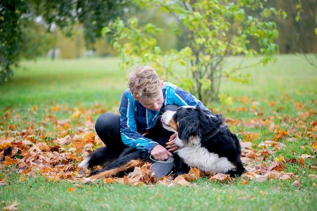 Ritratto all'aperto del ragazzo con il bovaro del bernese in autunno. amicizia dell'adolescente con l'animale domestico.