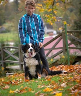 Outdoor ritratto di ragazzo con bovaro del bernese. amicizia di adolescente con animali da compagnia, ragazzo che cammina nella sosta di autunno