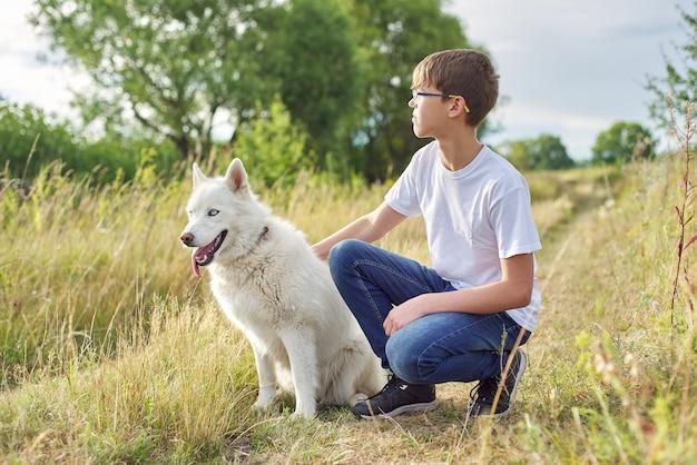 Ritratto all'aperto del ragazzo con il cane bianco