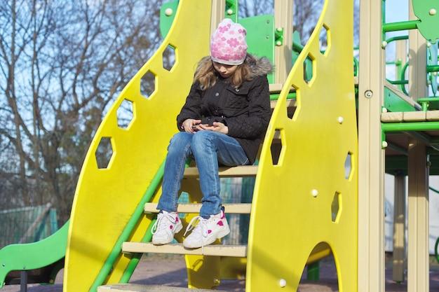 Ragazza del ritratto all'aperto con lo smartphone al parco giochi