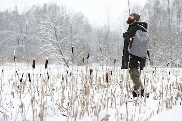 Ritratto all'aperto dell'uomo bello in cappotto e forfora. uomo barbuto nei boschi invernali.