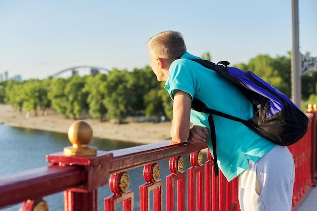 Ritratto all'aperto di un bel ragazzo adolescente di 15, 16 anni, con spazio per le copie. il ragazzo biondo con lo zaino guarda il fiume, in piedi sul ponte, la soleggiata giornata estiva al tramonto, lo stile di vita urbano