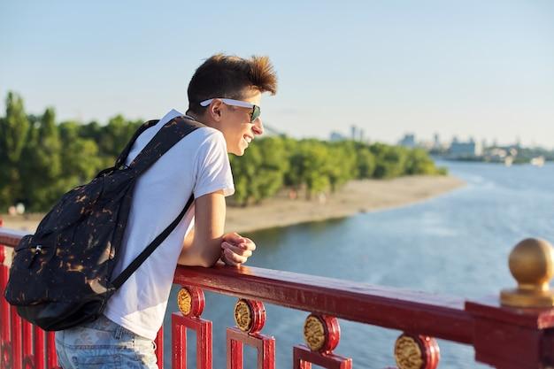 Ritratto all'aperto di un bel ragazzo adolescente di 15, 16 anni, con spazio per le copie. ragazzo con un taglio di capelli alla moda in occhiali da sole con zaino guarda il fiume, in piedi sul ponte, giornata estiva soleggiata al tramonto