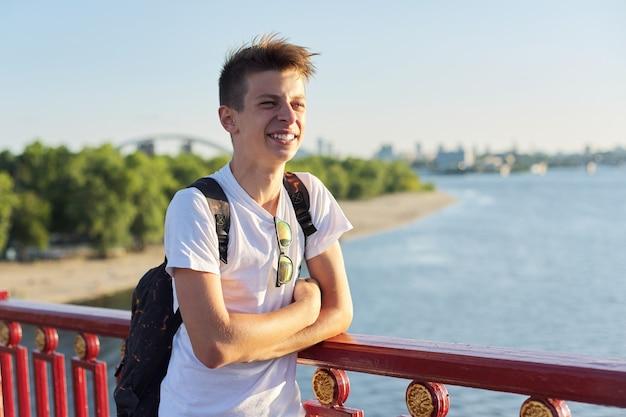 Ritratto all'aperto di un bel ragazzo adolescente di 15, 16 anni, con spazio per le copie. ragazzo con un taglio di capelli alla moda, con zaino in piedi sul ponte, giornata estiva soleggiata al tramonto, stile di vita urbano