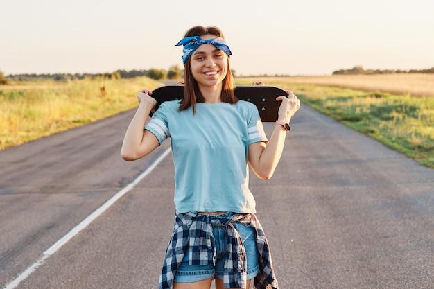 Ritratto all'aperto di felice donna dai capelli scuri che indossa maglietta blu, fascia corta e capelli, guardando la telecamera con un sorriso a trentadue denti, tenendo lo skateboard sulle spalle, esprimendo felicità.