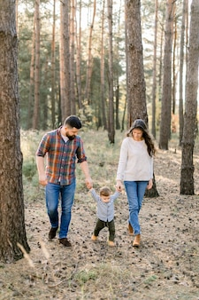 Ritratto all'aperto di una famiglia felice di tre persone, madre, padre, ragazzino, passeggiate fuori nella splendida pineta in una giornata autunnale