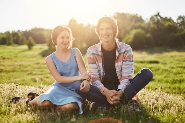 Il ritratto all'aperto della ragazza felice con capelli bobbed si è vestito in vestito blu che si siede vicino al suo amico divertendosi insieme godendo della bella natura