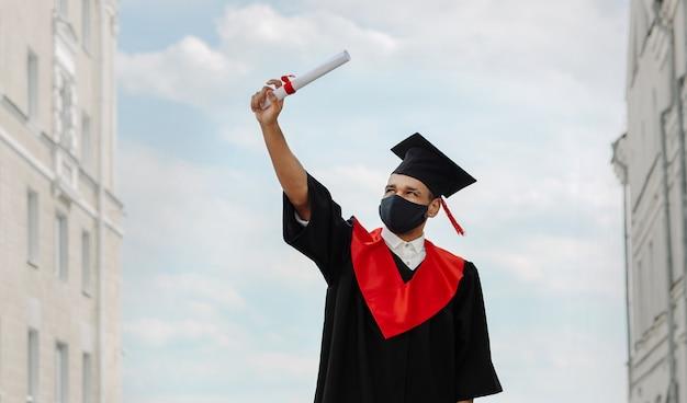 Ritratto all'aperto di happy grad student è in un mortarboard nero con nappa rossa e una maschera facciale in abiti da sera e guardando il diploma in mano