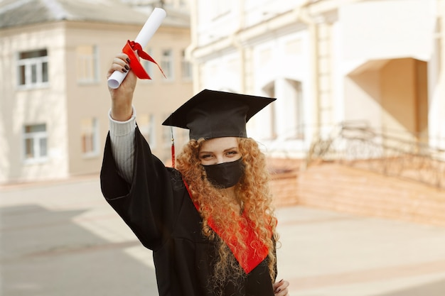 Il ritratto all'aperto di una studentessa felice che indossa una maschera facciale e un abito da laurea e un berretto quadrato con una nappa rossa mostra i suoi diplomi in attesa da tempo della classe del 2021