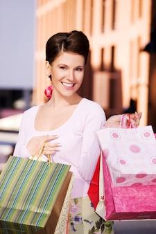 Ritratto all'aperto di donna felice con le borse della spesa