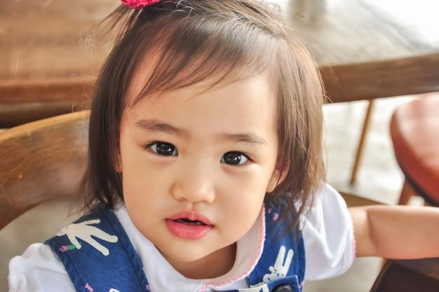 Ritratto all'aperto di piccola ragazza asiatica che porta il cappello rosso