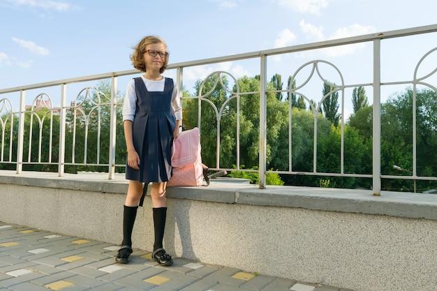 Ritratto all'aperto di piccola studentessa, ragazza con gli occhiali, uniforme con lo zaino