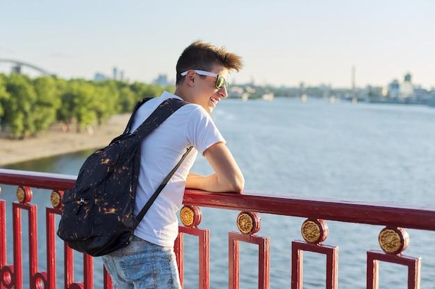 Ritratto all'aperto di giovane adolescente maschio sorridente con taglio di capelli alla moda che sta sul ponte sopra il fiume il giorno di estate soleggiato, spazio della copia