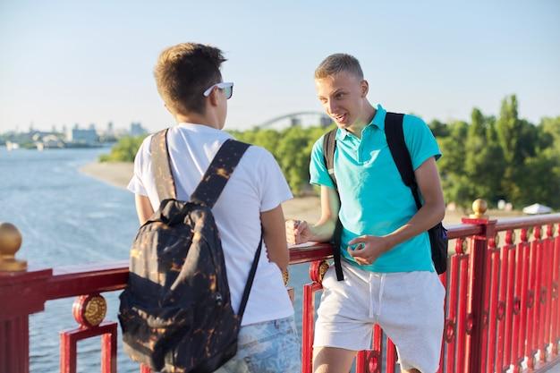 Ritratto all'aperto di due amici adolescenti ragazzi 15, 16 anni, ridendo, parlando in una giornata di sole, in piedi sul ponte sul fiume. stile di vita urbano, adolescenti, amicizia, comunicazione