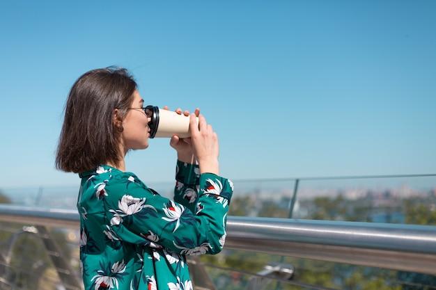 Outdoor ritratto di donna in camicia verde con una tazza di caffè che gode del sole, si trova sul ponte con vista mozzafiato sulla città al mattino