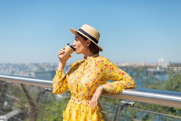 Outdoor ritratto di donna in abito estivo giallo e cappello con una tazza di caffè, godersi il sole, si trova sul ponte con vista mozzafiato sulla città