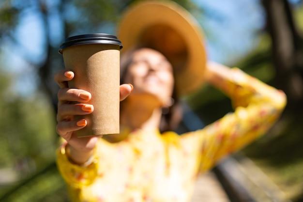 Outdoor ritratto di donna in abito estivo giallo e cappello con una tazza di caffè nel parco