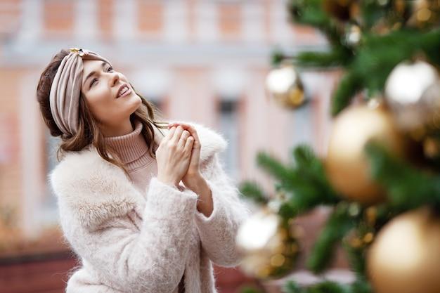 Ritratto all'aperto di giovane bella ragazza di sogno contro l'albero di abete decorato di natale.