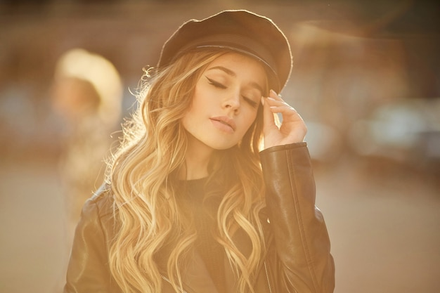 Outdoor ritratto di giovane bella donna alla moda e sensuale in giacca di pelle nera e cappello alla moda con trucco e occhi chiusi in posa in strada al tramonto