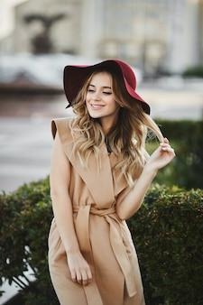 Outdoor ritratto di una giovane bella donna con lunghi capelli biondo platino in abito alla moda.