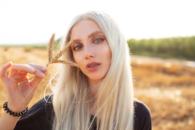 Ritratto all'aperto di giovane ragazza bionda di bellezza che tiene alcuni picchi di grano.