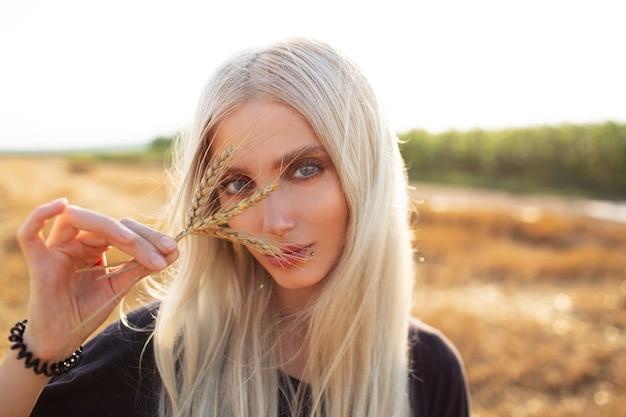 Ritratto all'aperto di giovane ragazza bionda di bellezza con punte di grano nelle mani.