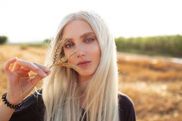 Ritratto all'aperto di giovane ragazza bionda che tiene i picchi di grano, nel campo.