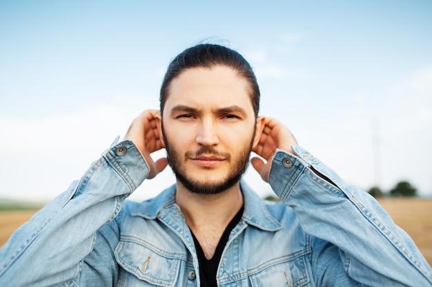 Ritratto all'aperto di giovane uomo bello, in giacca di jeans blu, il campo.