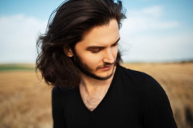 Ritratto all'aperto di giovane uomo bello con lunghi capelli scuri.