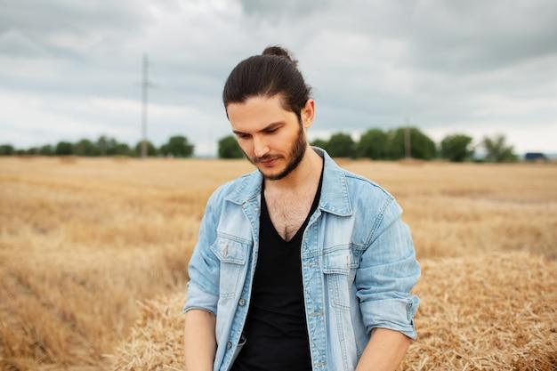 Ritratto all'aperto di giovane uomo in giacca di jeans, in piedi nel campo di grano.