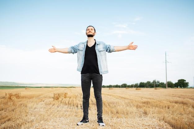 Ritratto all'aperto di giovane uomo con giacca di jeans, in piedi sul pagliaio.
