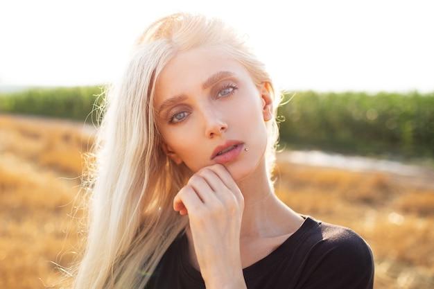 Ritratto all'aperto di giovane bella ragazza bionda, in piedi nei campi.