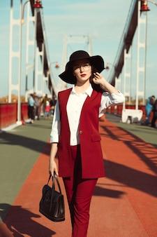 Ritratto all'aperto di giovane donna graziosa in costume rosso e cappello nero in posa sul ponte in una giornata di sole