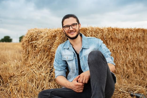 Ritratto all'aperto di giovane uomo sorridente, sullo sfondo del pagliaio.