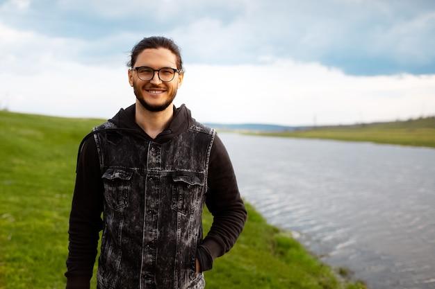 Ritratto all'aperto di giovane uomo sorridente vicino al fiume sul campo verde vago e sul cielo nuvoloso