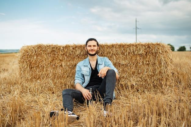Ritratto all'aperto di giovane uomo sorridente, seduto nel campo di grano.