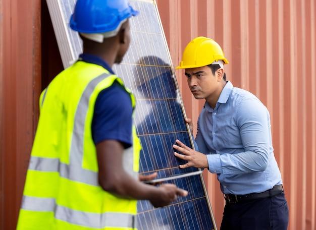Colpo all'aperto dell'ingegnere africano nero ispezionare il pannello solare elettrico che indossa l'elmetto protettivo, occhiali protettivi e dispositivi di sicurezza,