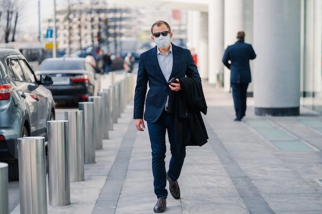 Il colpo all'aperto dell'uomo d'affari indossa la maschera medica protettiva, cammina nella via della città, vestito in abiti formali, tiene il telefono cellulare, va a lavorare
