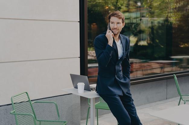 Colpo all'aperto dell'uomo occupato imprenditore risolve i problemi a distanza ha una conversazione telefonica