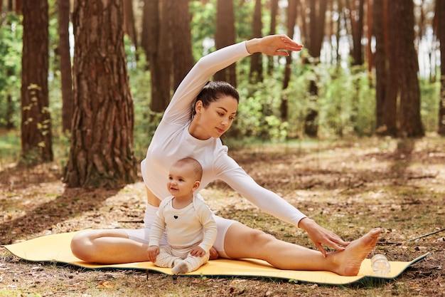 Colpo all'aperto della madre e del neonato in posa su karemat nella foresta